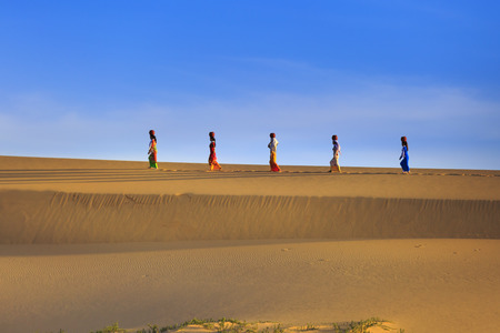 footprints in sand: Phan Rang town, Ninh Thuan province, Vietnam - November 26, 2016 : Cham women in traditional dress walking across sand dunes to collecting water near Phan Rang, Vietnam. Many Cham people retain their traditional ways.