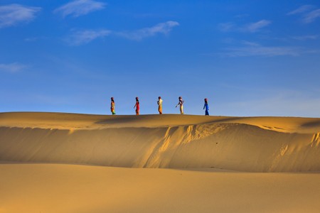Phan Rang town, Ninh Thuan province, Vietnam - November 26, 2016 : Cham women in traditional dress walking across sand dunes to collecting water near Phan Rang, Vietnam. Many Cham people retain their traditional ways.