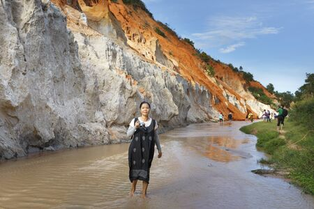 ne: Mui Ne, Phan Thiet city, Vietnam - November 27, 2016 : Woman so excited to be walking on feet in the Red Stream ( it also named Fairy Stream) located near the beach of Mui Ne, Binh Thuan Province, Vietnam