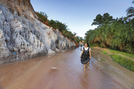 Mui Ne, Phan Thiet city, Vietnam - November 27, 2016 : Woman so excited to be walking on feet in the Red Stream ( it also named Fairy Stream) located near the beach of Mui Ne, Binh Thuan Province, Vietnam