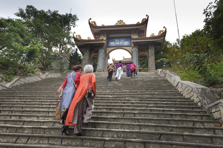Truc Lam zen monastery in Vinh Phuc Province, Vietnam - October 19, 2016: Vietnamese women in traditional dress Ao Dai walking toward the temple to pray  luck and happiness to your family and loved ones