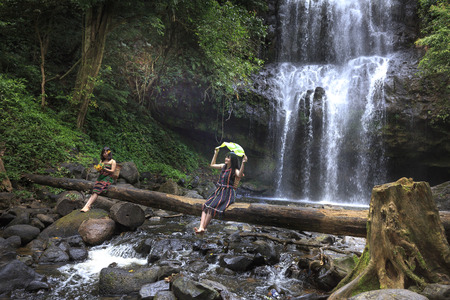 waterfall model: Dak Nong province, Viet Nam-January 14, 2017: the ethnic minority girls are having relaxing beside waterfall Editorial