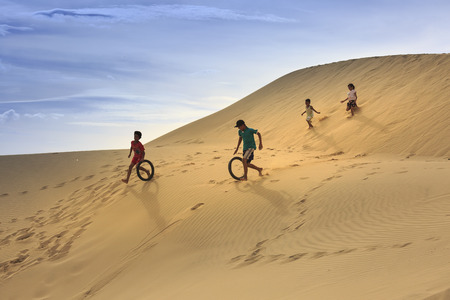 Phan Rang city, Vietnam - December 24, 2016: Children in the town Nangang, Phan Rang city playing with old tires on the sand dunes