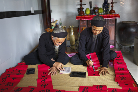 Vung Tau city, Vietnam - December 11, 2016: Two scholars writes Chinese calligraphy characters at Long Son, Vung Tau city. Calligraphy giving is a tradition popular for Tet holiday to Vietnamese People. Editorial