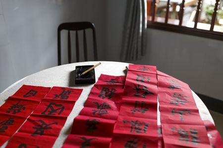 Chinese calligraphy with tools on red background.
