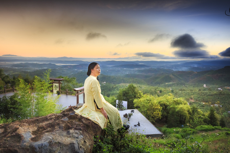 loc: Linh Qui Phap An temple, Bao Loc, Lam Dong Province, Vietnam - February 28, 2017 : woman wearing traditional dress aodai sitting relaxed on the yard of Linh Qui Phap An temple near Bao Loc town