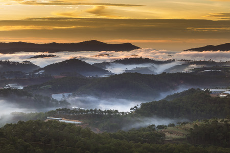 dalat: A view from mountains to the valley covered with foggy landscape. Dreamy Dalat city in the morning. Lam Dong province. Vietnam