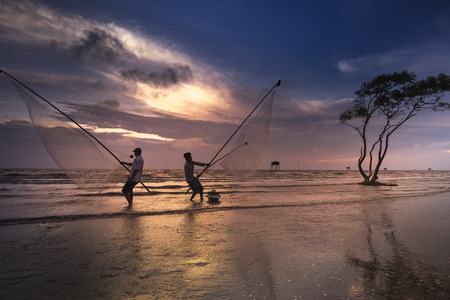 Tan Thanh beach, Go Cong district, Tien Giang province, Vietnam - March 19, 2017: Image of fishing village people using homemade tools to catch fish in sea at sunrise Editorial