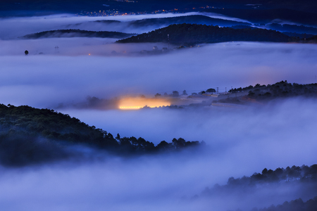 vietnamese ethnicity: The warm lights from the greenhouse to grow flowers in the dawn at Da Lat town. Da Lat always is  foggy town in the morning. Dalat is one of the most tourist beautiful and the famous town in Viet Nam. Stock Photo
