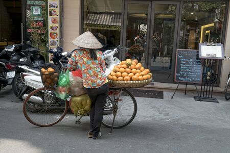 Old Town in Hanoi, Vietnam - March 4, 2018: A rural woman sells fruit in an ancient street in Hanoi, Vietnam. 報道画像