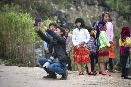 Ta Xua, Son La Province, Vietnam - January 16, 2018: Photographer with hmong children in Son La, Vietnam. In time Hmong New Year at the end of the Lunar year, they often wear the most beautiful costu 報道画像