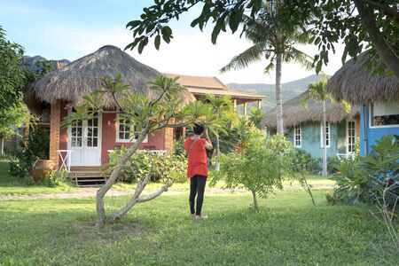 Ninh Van Commune, Khanh Hoa Province, Vietnam - June 26, 2018: A female tourist is taking pictures of the colorful little bungalow in Backpacker Hostel in Ninh Van commune, Khanh Hoa province, Vietnam