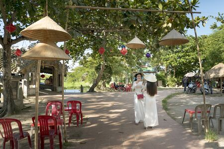 Thanh Thuy Chanh Village, Hue city, Vietnam - June 30, 2018: Two Vietnamese girls are gentle in culture traditional white long dress is taking self-portrait for each other at Thanh Thuy Chanh Village in Hue city, Vietnam
