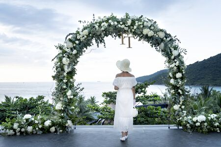 Intercontinental Peninsula Resort Da Nang, Vietnam - July 8, 2018: Beautiful young girl in a long white dress standing next to the gate of white roses. Beautiful girl, mysterious love concept Editorial