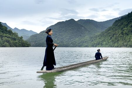 Ba Be lake, Bac Kan province, Vietnam - July 14, 2018: Ethnic Tay women in traditional costume are the rowing dugout (the boat made from a single tree trunk ) on Ba Be Lake. Ba Be Lake is a famous tourist destination of Bac Kan Province, Vietnam