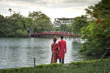 Hanoi capital, Vietnam - July 16, 2018: A couples in traditional ao dai costume are looking at the The Huc ancient bridge on Hoan Kiem Lake- which is the center of the capital Hanoi, Vietnam.