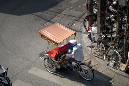 Hanoi capital, Vietnam - July 12, 2018: Cyclo or pedicab driver on Hanoi street. Cyclo is one of the most favorite vehicles for tourist when coming to Vietnams cities.