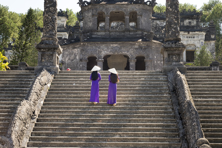 Two Vietnamese girls are gentle in culture traditional purple long dress at the Tomb of Khai Dinh King at Hue city, Vietnam