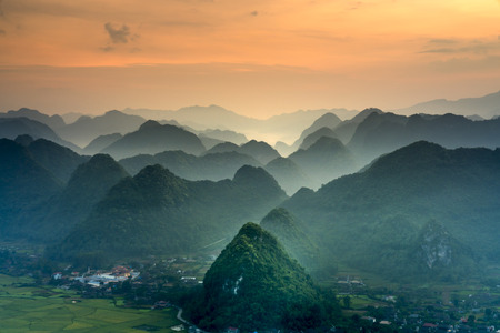 The magical scene of the mountains resemble the successive message they are covered with layers of lush green vegetation at dawn in Bac Son district Lang Son Province, Vietnam 写真素材