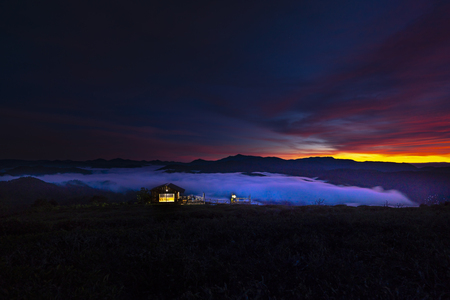 The dreamlike view of a small lovely wooden house, located in the edge of the valley  with full of the clouds in the early morning, when the sun is rising. 스톡 콘텐츠