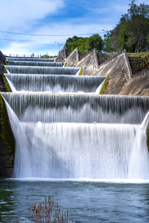spillway waterfall, water flowing over the dam at deteriorating reservoir Фото со стока