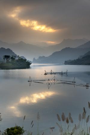 Nuvole fantastiche e cielo al tramonto. Tempo tranquillo. Cielo colorato che si riflette nel lago. Silhouette. L'estate sta arrivando. Splendido scenario tranquillo della foresta di montagna nel comune di Th.Lam, provincia di T. Quang, VN