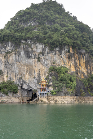 Thac Bo Cave, Thung Nai Commune, Cao Phong District, Hoa Binh Province, Vietnam - January 9, 2019: A temple is located at the main entrance to Thac Bo Cave on Hoa Binh Lake. This is a famous tourist Stok Fotoğraf