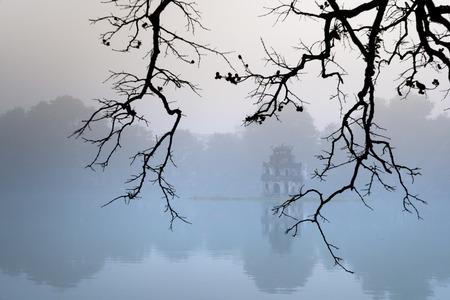 Hoan Kiem Lake ( Ho Guom) in the center of Hanoi in the fog in the morning. Hoan Kiem Lake is a famous tourist place in Hanoi Stock Photo
