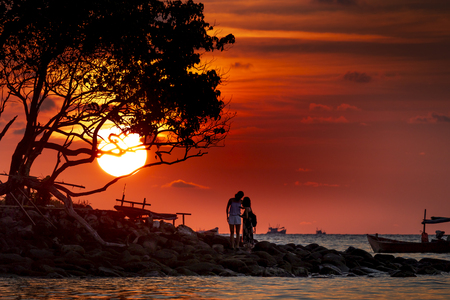 The silhouette of couple enjoyed the sunset of Koh Rong samloem island in Cambodia in paradise island Villa Koh Rong Samloem. Cambodia. This is a small island that attracts many visitors from all over Stock Photo