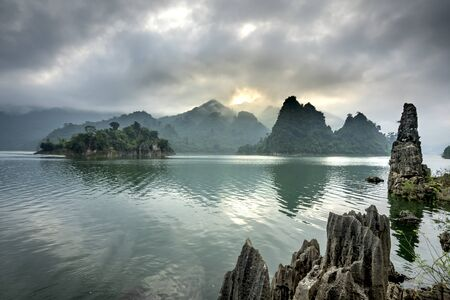 Dawn on Na Hang lake in Tuyen Quang province, Viet Nam. This natural lake has a green watercolor. It is located between the majestic cliffs. Every year this place attracts many tourists to visit