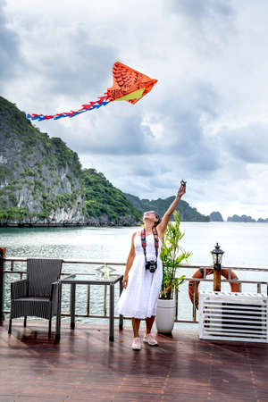 Ha Long Bay, Quang Ninh Province, Vietnam - July 3, 2020: Female tourist excited with colorful kite on the deck. Beautiful scenery of Ha Long Bay. North Vietnam