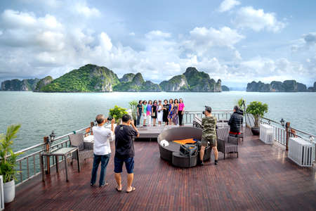Ha Long Bay, Quang Ninh Province, Vietnam - July 3, 2020: Tourists from the open top deck of the ship admiring the magnificent scenery of Halong Bay. North Vietnam.