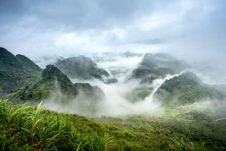 the morning looking at the majestic landscape with fog and clouds in the mountainous areas of Cao Bang province, Viet Nam. The scene is fanciful and poetic