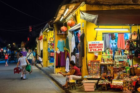 sidewalk talk: Hoi An, Vietnam - September 01, 2013: Tourists are walking in the street at night