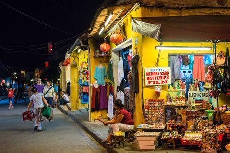 sidewalk talk: Hoi An, Vietnam - September 01, 2013: Tourists are walking in the street at night