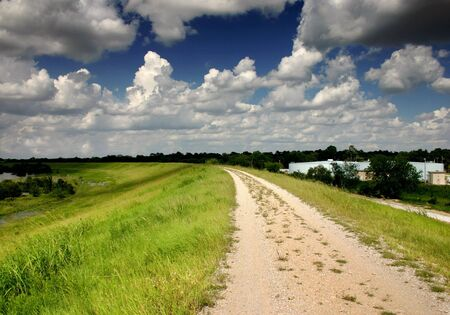 a joggingcycling trail with grassy areas and clouds Stock Photo