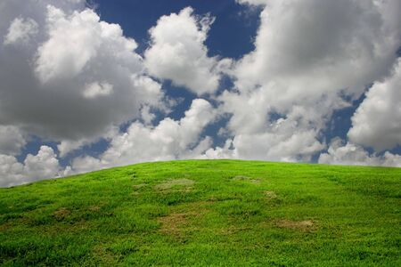 clouds passing over a green hill