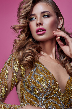 Beautiful woman blonde fashion model in gold dress with perfect make up. Isolated on a pink background. Stock Photo