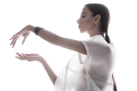 Side view of beautiful brunette wearing modern transparent outfit and accessories standing on glowing white light with sensual hands.