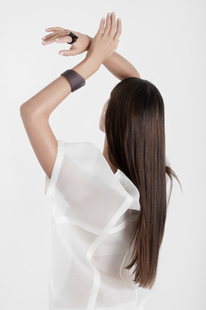Back view of brunette with long hair wearing white transparent outfit holding hands up sensually on white backdrop.