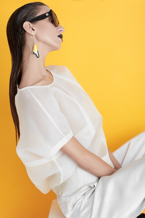 Side view of confident fashionable model in white gown and black accessories sitting with wet hair on yellow.