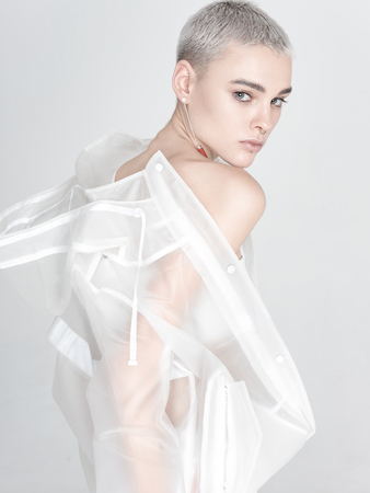 Side view of beautiful young woman with short hair looking at camera and putting on translucent trendy jacket against white background