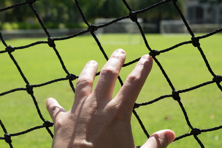 waiting glance: Mans hand extended to touch the mesh of a football field.
