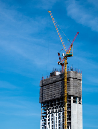 Industrial construction crane for high rise building with blue sky background Stock Photo