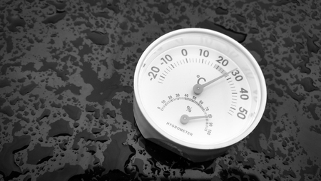 assays: Analog hygrometer putting on a black background filled with drop of water after rain. Stock Photo