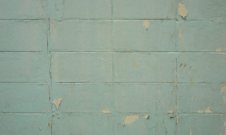 Concrete or cement block wall in broken condition with light blue color and chipping paint, selective focus.