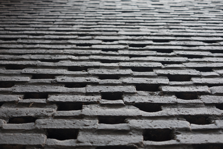 Brick in black colour work wall pattern in one point perspective view, craftmanship in construction building, selective focus. Stock Photo