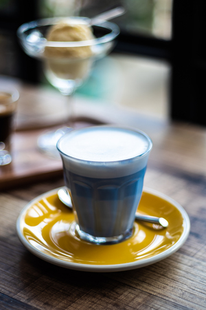 Hot milk with butterfly pea mixed and milk froth on the top of glass, decorate with yellow disk on wooden table in cafe shop mood and tone, selective focus.