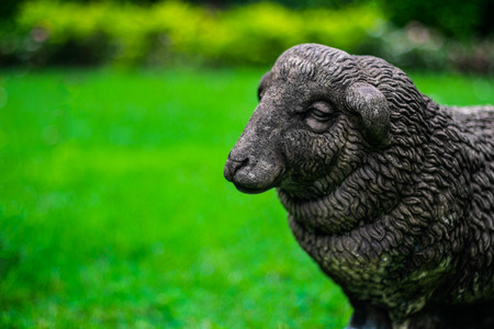 Sculpture of sheep  on greenery blurred background, selective focus.