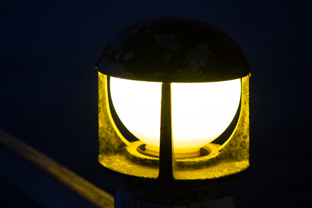 Close up of vintage bollard lamp on wooden railing with bokeh background in night time, selective focus.
